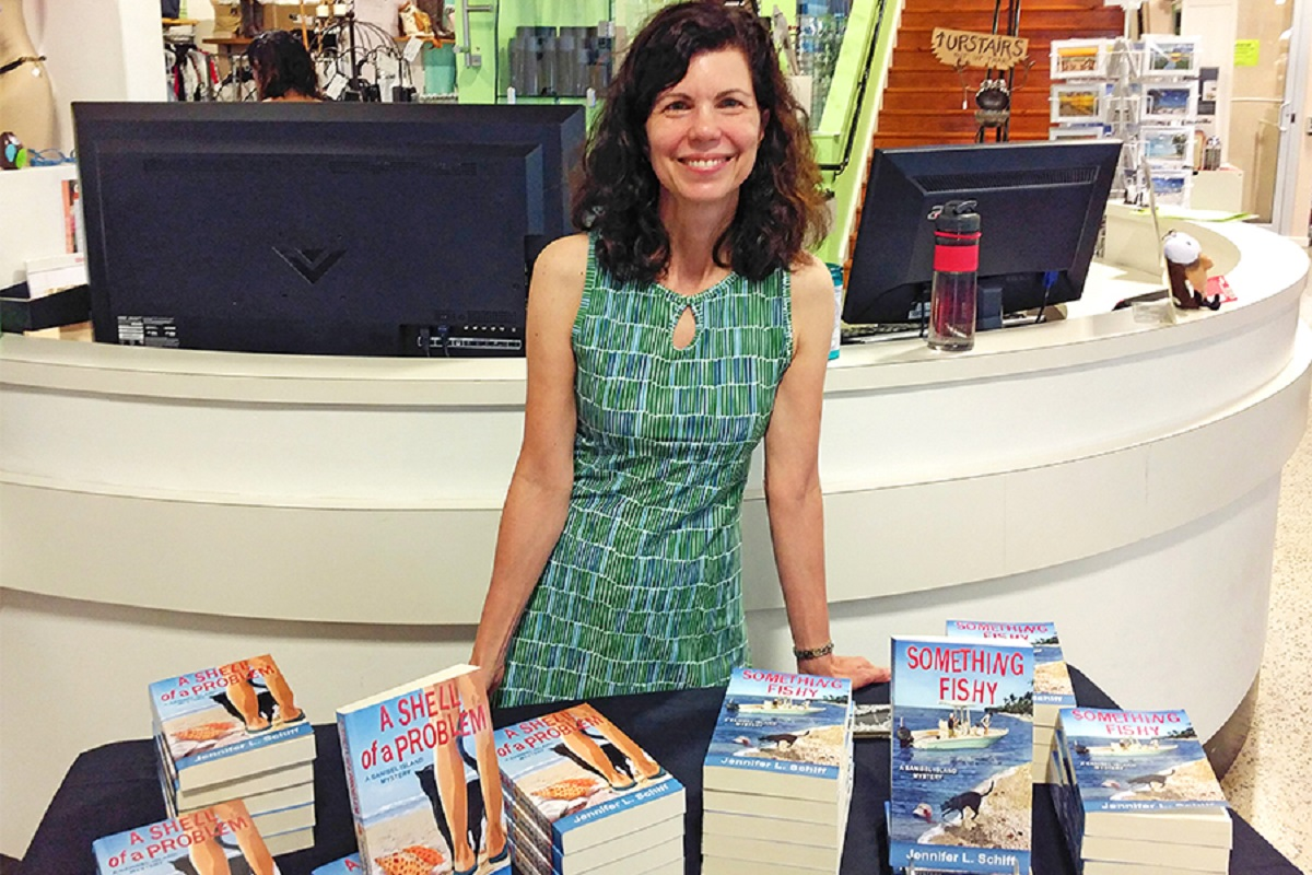 Author Jennifer L. Schiff with stacks of her book A Shell of a Problem