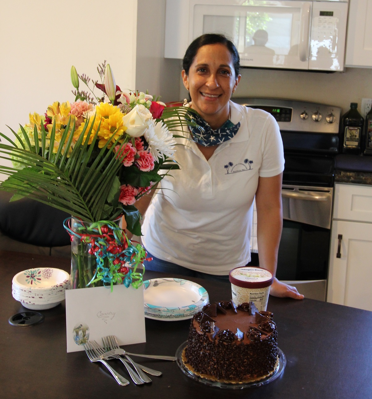 Conchy, a female, standing next to a floral arrangement and a chocolate cake in front of her