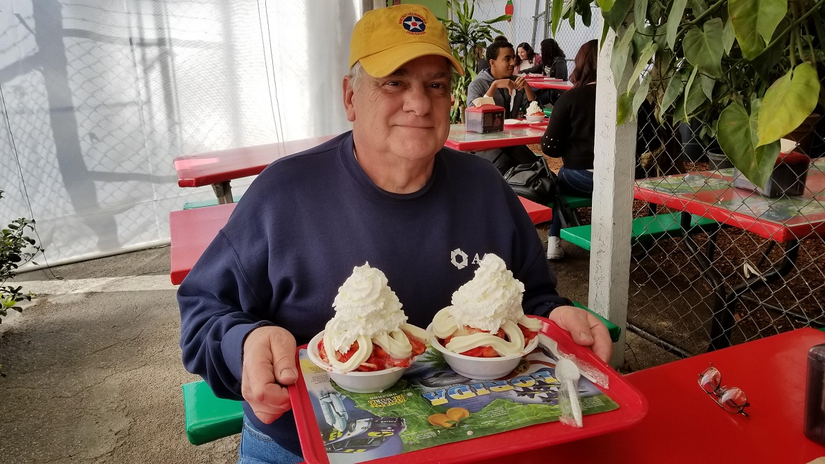 Older man holding a tray with two bowls of berries with whipped cream on top