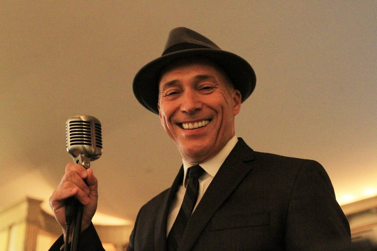 Photo of Michael Dutra holding a microphone